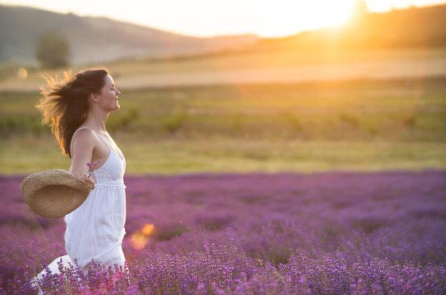 Beautiful woman enjoying the sun in a lavender field